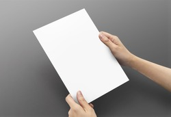 Close up women hands holding paper blank a5 size for design paper on dark grey background.