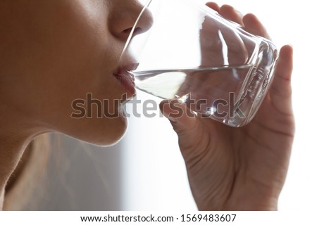 Close up women profile face and hand holding glass of still water, young female drinks clear aqua reduces thirst, losing weight and dieting, flushes body waste, boosts skin health and beauty concept