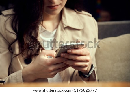 Close up women's hands holding smartphone. Young woman sitting in coffee shop at wooden table,  #1175825779