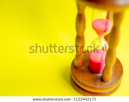 Close-up Wooden Vintage Hourglass with Pink Sand on Yellow Background, Sand Running through the Bulbs for Measuring The Passing Time in A Countdown to Deadline. #1122442175