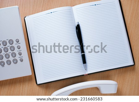 Close up Work Area of Telephone Officer with Ready Notebook and Pen for Appointments.