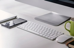 Close up working place for start up business with desktop computer, white keyboard, mouse, smartphone and laptop.