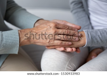 Close up wrinkled mommys hands covering grown up daughters, showing support and care. Loving mature mother having sincere conversation with millennial daughter, giving psychological help, advices.