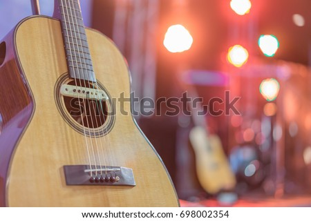 Close up yellow acoustic guitar on a stand in front of a stage set up for an upcoming concert. #698002354