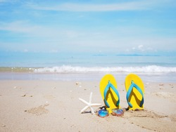 Close up Yellow sandal sunglasses and white starfish on the beach over sea background. Summer holiday concept.