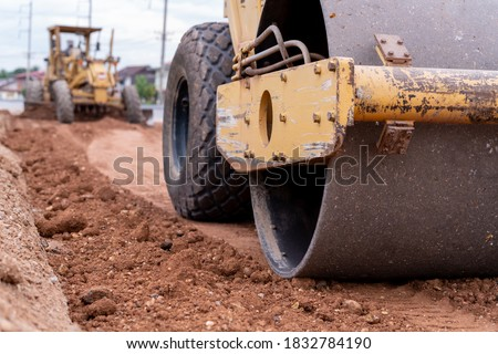 Close up Yellow vibratory soil and Motor Grader Civil compactor working on road construction site, Yellow vibratory soil compactor in road construction site Foto stock ©