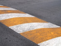 close up yellow white stripe speed bump on asphalt road, traffic warning signs to drive vehicle slow down