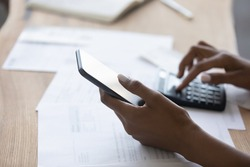 Close up young african american biracial woman holding smartphone in hands, calculating domestic expenses or bills, managing medical or financial investments using mobile e-banking application.