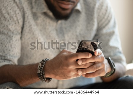 Close up young african american man sitting on couch, holding smartphone in hands, typing message, posting in social media, chatting with friends or relatives, playing online game, doing purchases. #1486444964