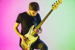 Close up young and joyful caucasian musician playing bass guitar on gradient studio background in neon light. Concept of music, hobby, festival. Colorful portrait of modern artist. Inspired