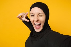 Close up young arabian muslim woman in hijab black clothes doing selfie shot on mobile phone isolated on yellow wall background studio portrait. People religious lifestyle concept. Mock up copy space