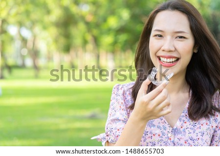 close up young beautiful asian woman smiling with hand holding dental aligner retainer (invisible) at outdoor nature park and garden background for beautiful teeth and dental treatment course concept #1488655703