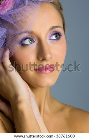 Close-up young beautiful woman in violet bonnet in studion shot on gray background