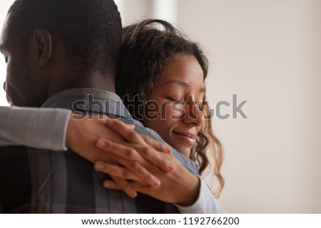 Close up young black american wife embracing husband. Portrait of woman with closed eyes, man rear view. Attractive affectionate couple in love, romantic relationship support and gratefulness concept