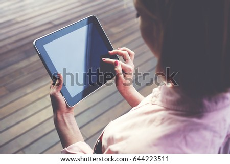 Close up young blonde female student using touchpad against wooden background, freelancer girl working on her digital tablet with big copy space, hipster woman browsing with touchscreen device #644223511