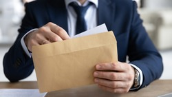 Close up young businessman entrepreneur in formal wear opening envelope with paperwork correspondence, male manager employee unpacking banking notification, law order or paper document at workplace.