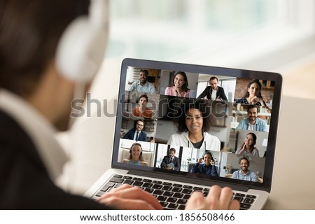 Close up young businessman in headphones holding online video call conference with african american female team leader and diverse colleagues using computer application, distant working communication.