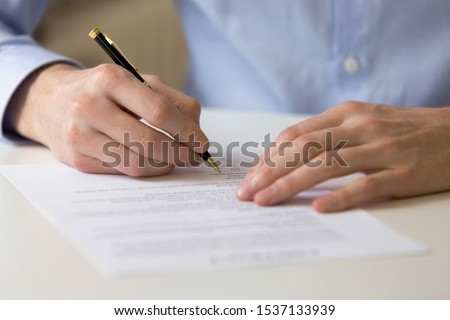 Close up young businessman sitting at table, filling in questionnaire, financial document, bank loan form. Successful male entrepreneur signing contract agreement, putting signature on franchising.