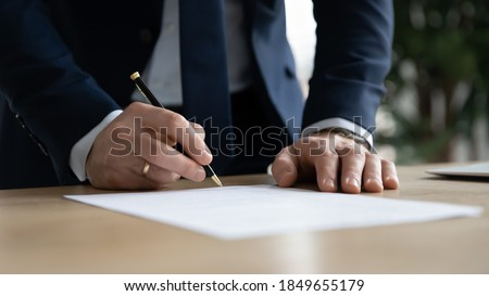 Close up young businessman standing near table with pen in hands, ready signing profitable offer agreement after checking contract terms of conditions, executive manager involved in legal paperwork.