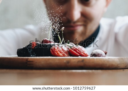 Close up young chef decoration dessert dish in bakery.