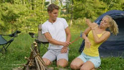 CLOSE UP: Young couple camping in wild gets attacked by buzzing mosquitoes. Funny shot of man slapping his girlfriend with a fly swatter as the couple on camping trip gets swarmed by annoying bugs.