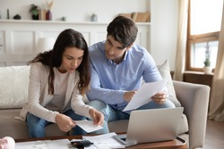 Close up young couple checking mortgage or loan agreement, financial documents together, using laptop and calculator, sitting on couch at home, focused wife and husband calculating domestic bills