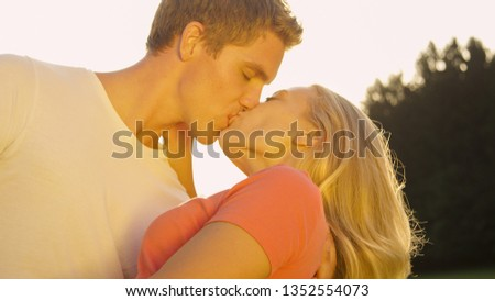 CLOSE UP: Young couple madly in love kisses passionately during a date at golden sunset. Gorgeous blonde haired girl leans back in her boyfriend's embrace and gets kissed on a sunny spring morning.