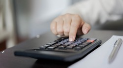 close up young employee woman hand pressing on calculator to counting and planning about spending salary monthly for manage to invest , insurance, loan concept