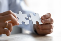 Close up young entrepreneur putting different parts of puzzles together, making business decision, finding creative logical problem solution or developing strategy brainstorming alone in office.