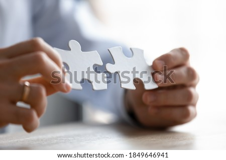Close up young entrepreneur putting different parts of puzzles together, making business decision, finding creative logical problem solution or developing strategy brainstorming alone in office. Foto d'archivio ©