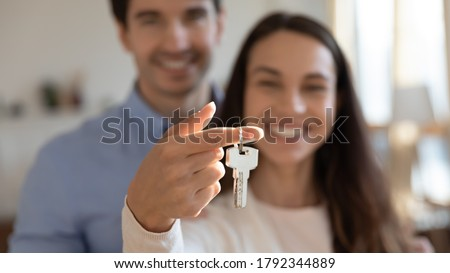 Close up young excited couple showing keys in hands to camera. Happy homeowners celebrating moving in new apartment or last banking mortgage payment, feeling glad of purchasing property, real estate. Foto stock ©