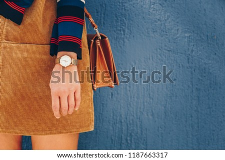 close up, young fashion blogger wearing a corduroy dress and a white and golden analog wrist watch. checking the time, holding a beautiful  leather purse. street style fashion details.