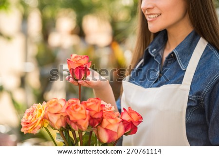 Close-up. Young female florist holding a rose in flower shop.