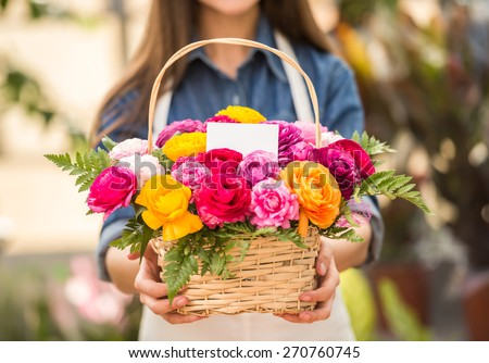 Close-up. Young female florist holding bouquet of flowers in shop. Focus on bouquet.