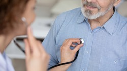 Close up young female general practitioner or cardiologist using stethoscope, checking heartbeat or listening lungs sounds of middle aged elder retired male patient at checkup appointment in hospital.