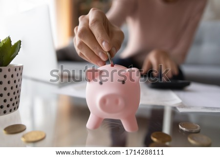 Close up young female putting coin in piggy bank. Woman saving money for household payments, utility bills, calculating monthly family budgets, making investments or strategy for personal savings.