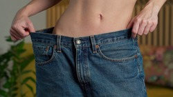 Close up young fitness woman with a slim waist slender figure tries on big pants and shows how to lose weight to the camera