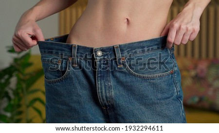 Close up young fitness woman with a slim waist slender figure tries on big pants and shows how to lose weight to the camera Сток-фото ©