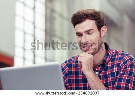 Close up Young Handsome Man in Checkered Shirt Chatting to Someone Using Laptop Computer