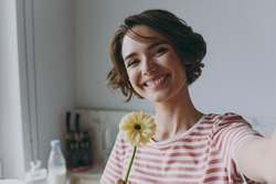 Close up young housewife woman 20s in casual clothes striped t-shirt holding flower gerbera doing selfie shot on mobile phone cooking food in light kitchen at home alone Healthy diet lifestyle concept