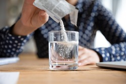 Close up young indian woman pouring soluble anti-influenza powder in glass of water. Sick millennial girl student feeling unwell, relieving grippe fever flu symptoms, high temperature, headache.