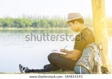 Close up Young man is currently writing notes with a pencil  under a tree near the pool. - Shutterstock ID 584814193
