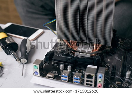 Close up. Young Man Repairing Motherboard from PC. Repair Shop. Worker with Tools. Computer Hardware. Magnifying Glass. Soldering Iron. Digital Device. komputer on Desk.  Zdjęcia stock ©