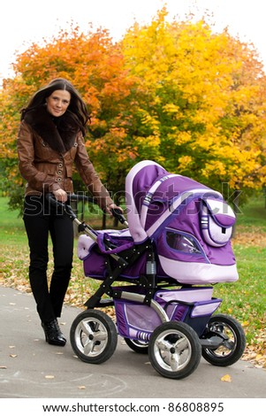 close-up young mother with stroller in autumn of city park