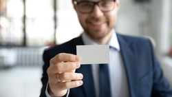 Close up young smiling confident businessman showing blank mock up empty name card to camera, giving personal professional contact information to client, self -introduction acquaintance concept.