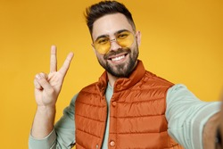 Close up young smiling happy fun caucasian man 20s in orange vest mint sweatshirt glasses doing selfie shot on mobile phone show victory v-sign gesture isolated on yellow background studio portrait.