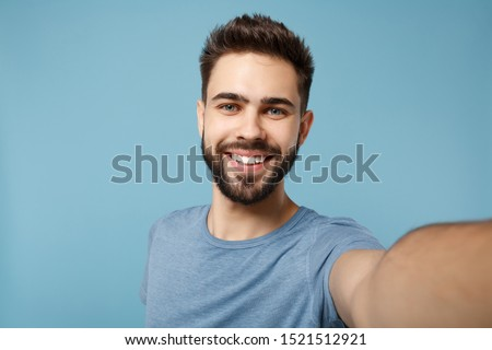Close up Young smiling man in casual clothes posing isolated on blue wall background, studio portrait. People sincere emotions lifestyle concept. Mock up copy space. Doing selfie shot on mobile phone