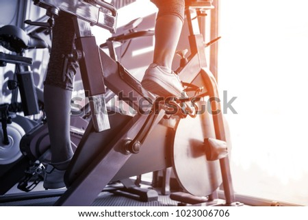 Close up young sport woman exercising on bicycle workout at fitness gym