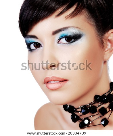 Close-up young woman beautiful face with stylish fashion eye make-up. Studio shot on white background.