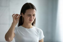 Close up young woman cleaning ears, using cotton bud after shower, feeling pain, beautiful female wearing white t-shirt standing in bathroom, morning routine, personal hygiene concept